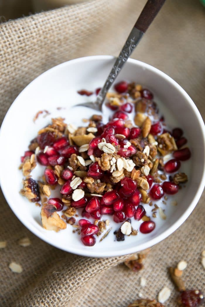 Image of a white bowl filled with granola that's been toasted with autumn spices, milk, and pomegranate arils.