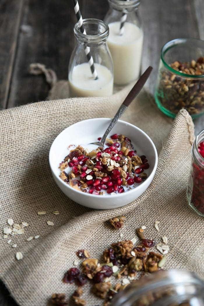 Image of a table with a canister of spiced granola, bowl of pomegranate arils, cup of milk, and bowl filled with a spoon and a serving of crunchy fall spiced granola with milk.
