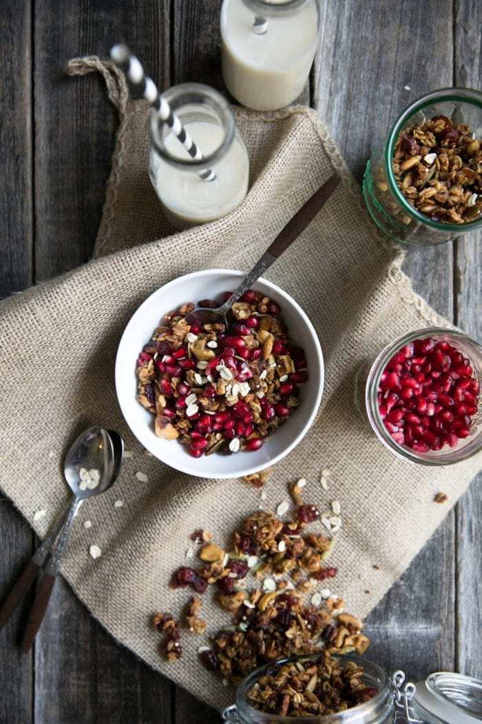 Overhead image of a table with a canister of spiced granola, bowl of pomegranate arils, cup of milk, and bowl filled with a spoon and a serving of crunchy fall spiced granola.