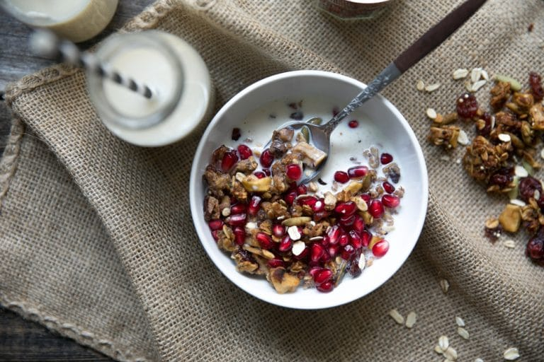 White bowl filled with milk and homemade fall granola made with rolled oats, quinoa, nuts and seeds, and pomegranate arils.
