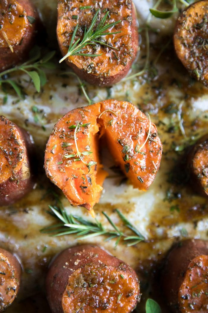 Roasted sweet potatoes on a large baking sheet covered with melted butter, brown sugar, and fresh herbs.