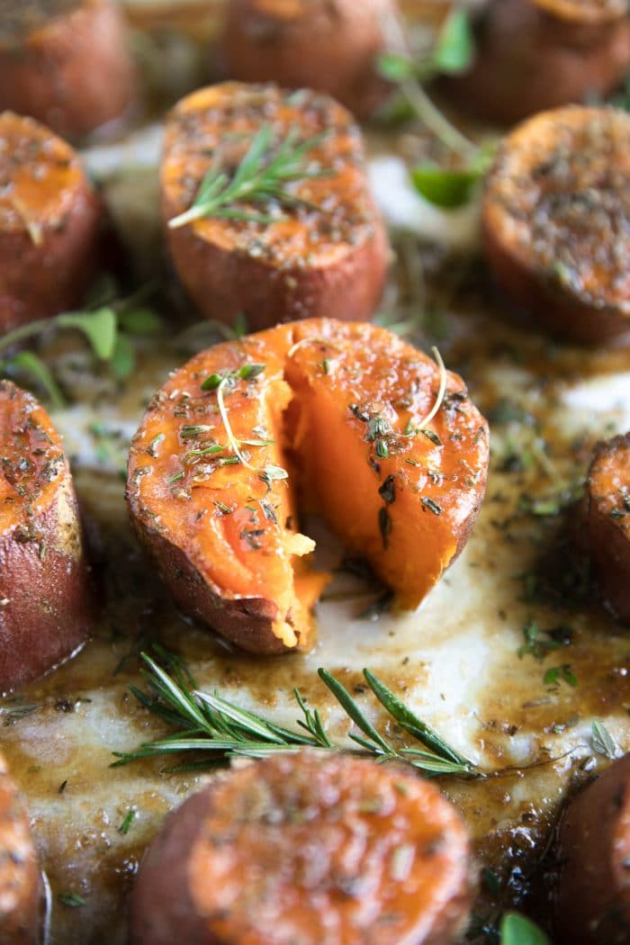 Tender oven-roasted sweet potatoes on a large baking sheet covered with melted butter, brown sugar, and fresh herbs.