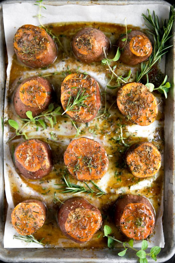Overhead image of Tender oven-roasted sweet potatoes on a large baking sheet covered with melted butter, brown sugar, and fresh herbs.