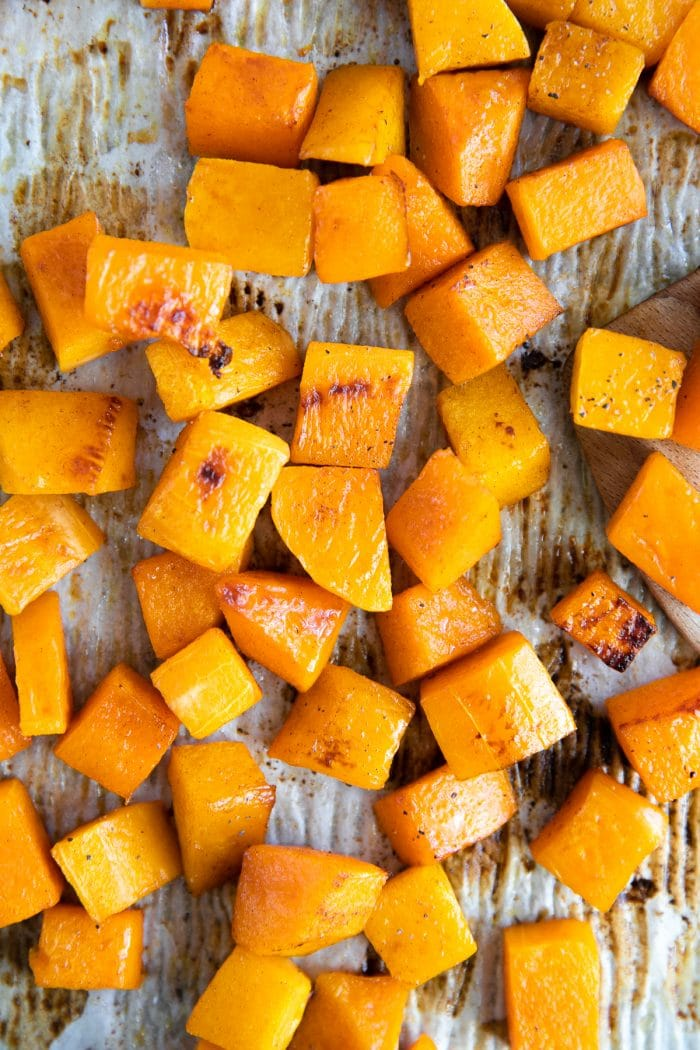 Roasted cubes of butternut squash on a baking sheet.