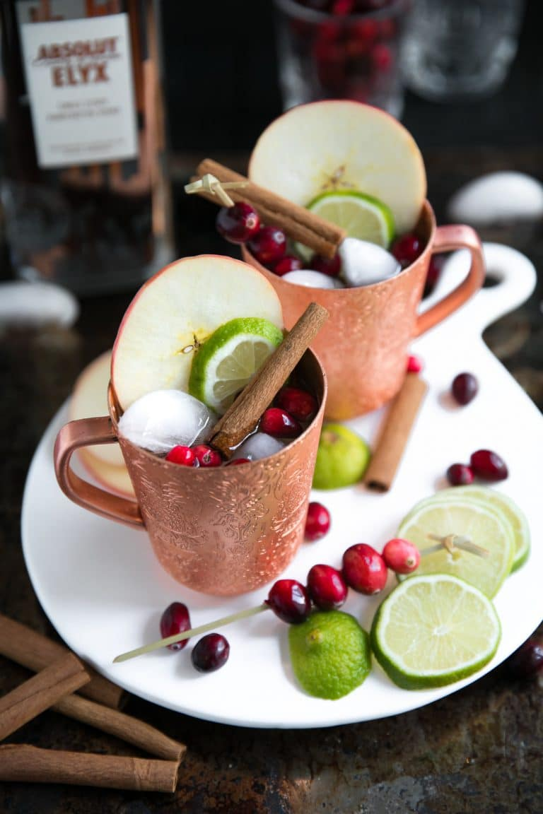 Copper mugs filled Cranberry Apple Cider Moscow Mule garnished with apple and cinnamon sticks