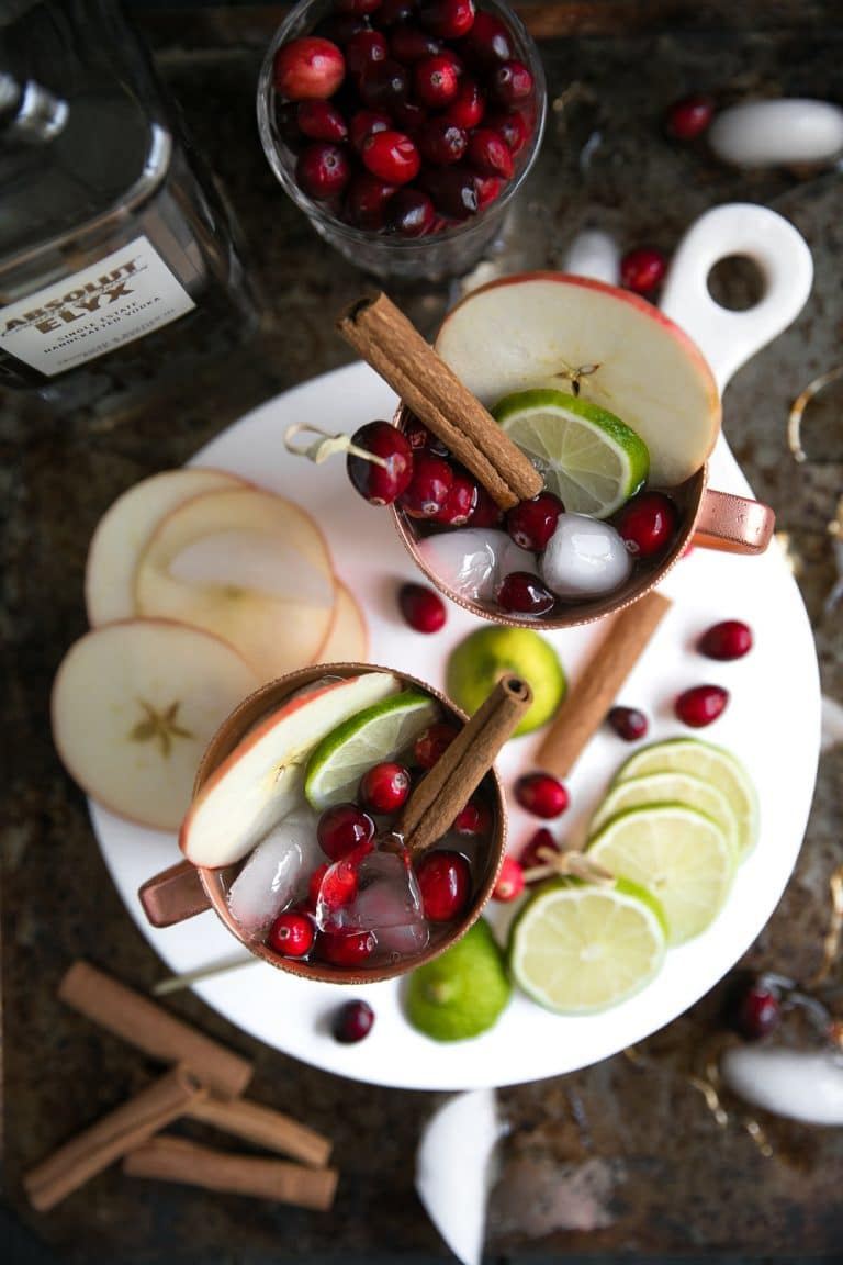 overhead image of Copper mugs filled Cranberry Apple Cider Moscow Mule garnished with apple and cinnamon sticks