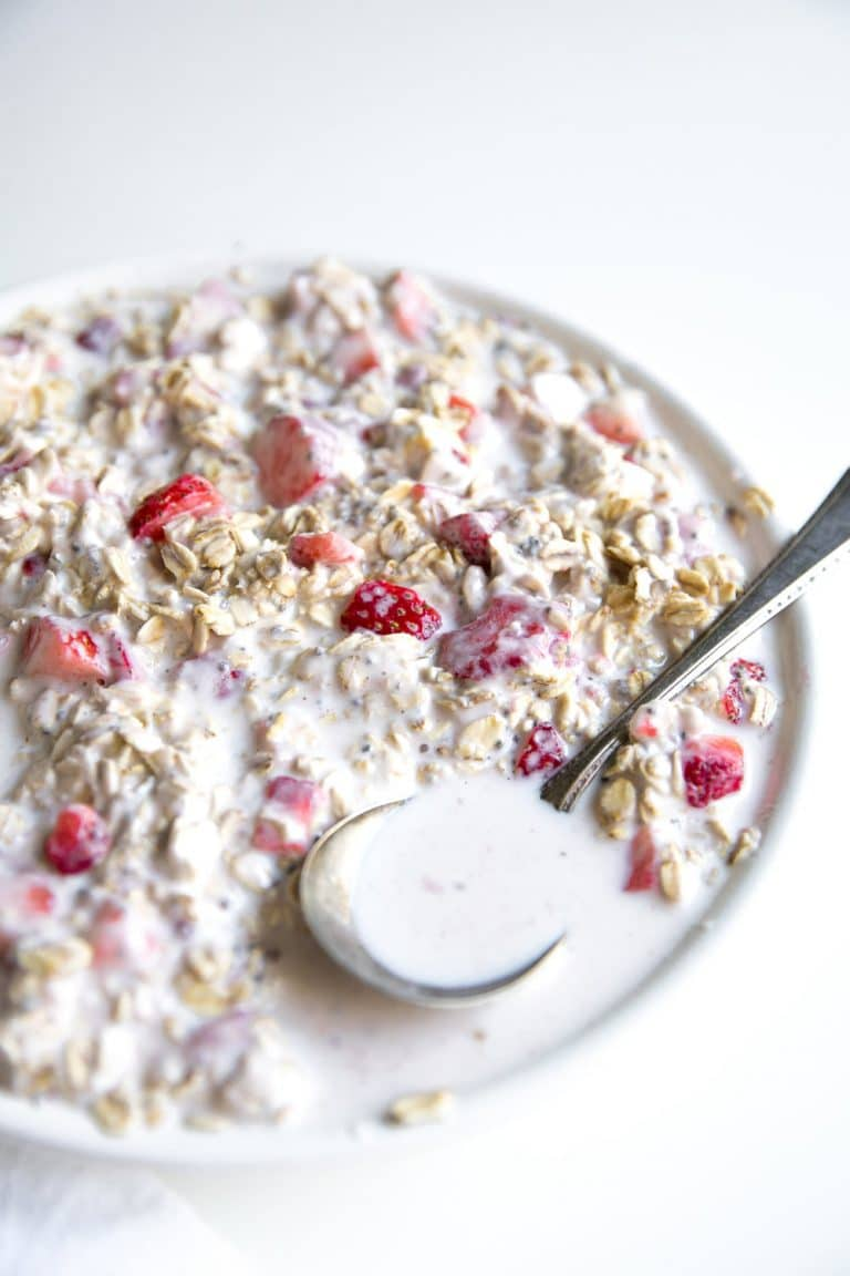 Close up image of a large white bowl filled with milk and overnight oats with yogurt