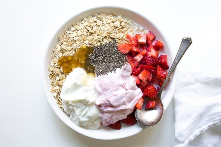 Bowl with Oats, milk, strawberry and vanilla yogurt, chopped strawberries, chia seeds, and honey.