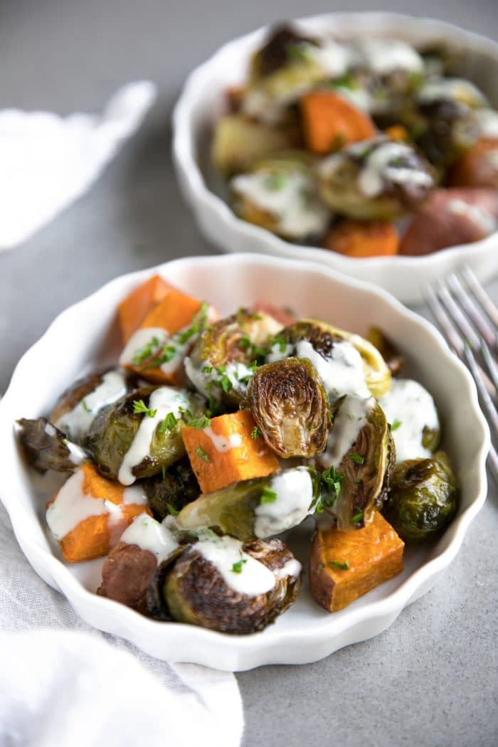 Small white dishes filled with roasted brussels sprouts and sweet potatoes drizzled with homemade tahini sauce.