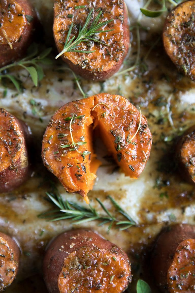 close-up image of one roasted sweet potato split in half with brown sugar and fresh herbs