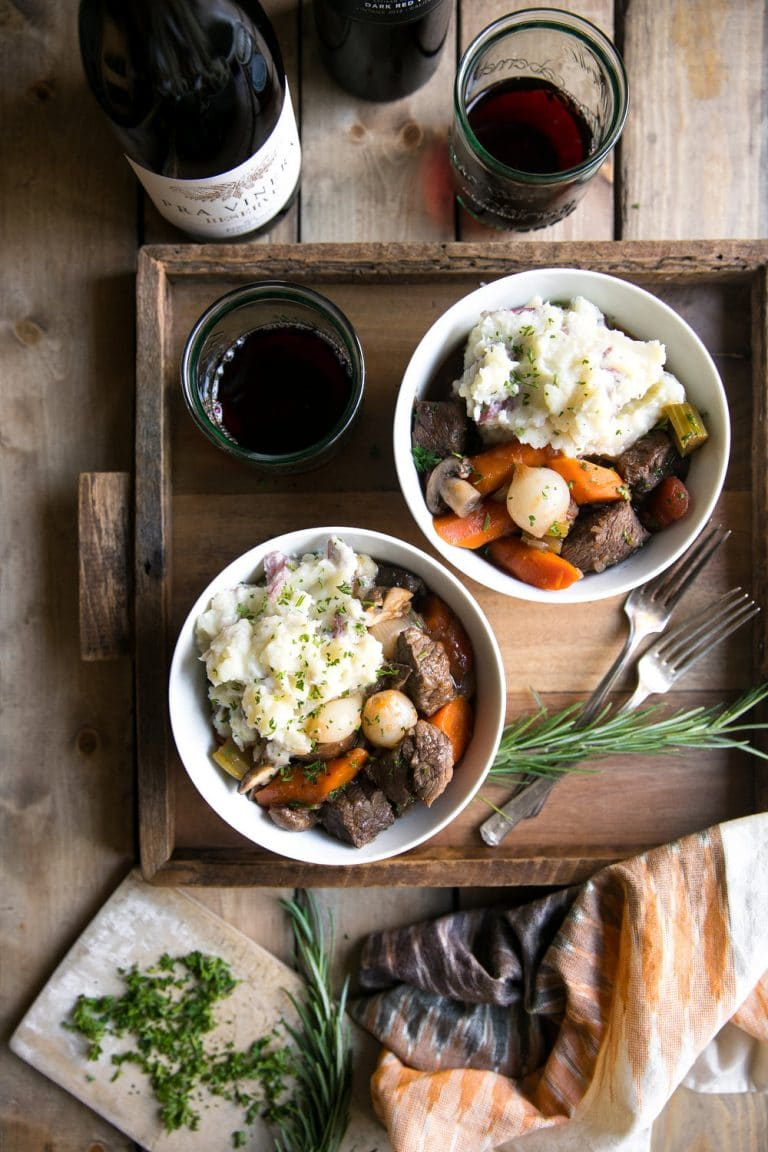 bowls with Best Slow Cooker Beef Bourguignon and mashed potatoes with wine glasses