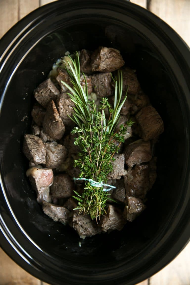 Slow Cooker filled with beef chunks and fresh herb bouquet.