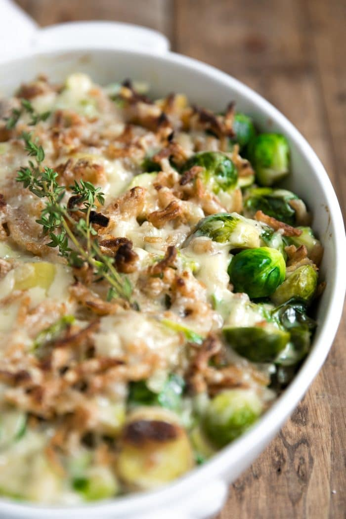 White au gratin pan filled with Brussels sprout and potato casserole topped with cheese and fried onions and baked until melted and golden.