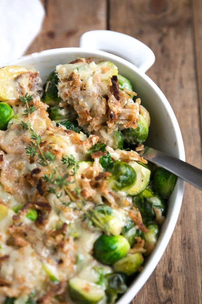 Large spoon scooping a large helping of Brussels Sprout and Potato Gratin from a white au gratin dish.