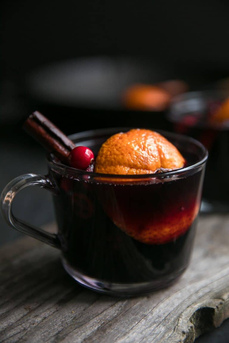 Glass of mulled wine garnished with orange, cinnamon stick, and cranberries.
