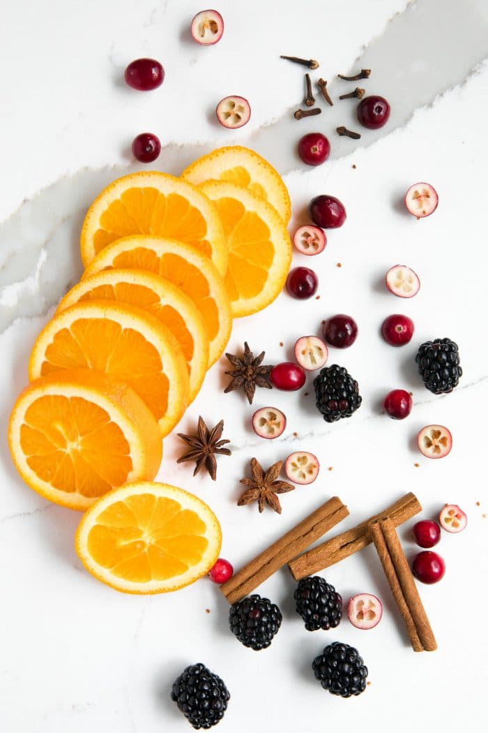 Overhead image of orange slices, whole cloves, cinnamon sticks, whole star anise, blackberries, and cranberries.