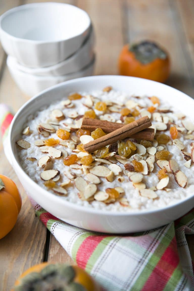Large white bowl filled with creamy rice pudding topped with raisins, almonds, and cinnamon.