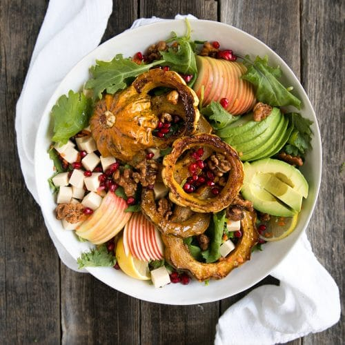 A plate of food on a wooden table, with Autumn Quinoa Apple Salad with Acorn Squash