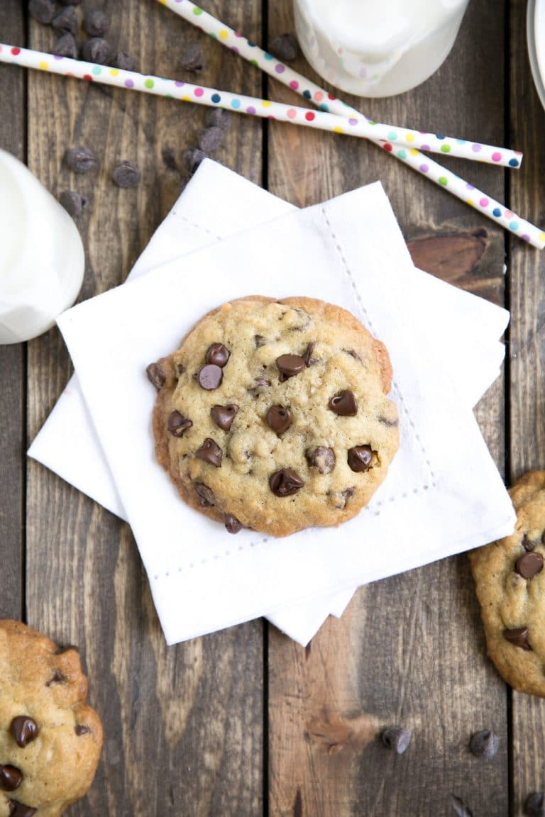 Browned butter chocolate chip cookie on a white napkin with small jug of milk