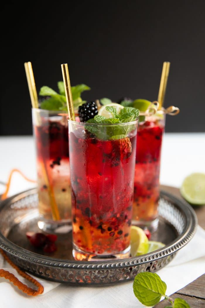 Blackberry Cranberry Moscow Mules garnished with fresh mint and lime wedges.