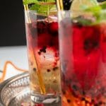 Two highball glasses filled with ginger beer, vodka, and fresh blackberries and raspberries.