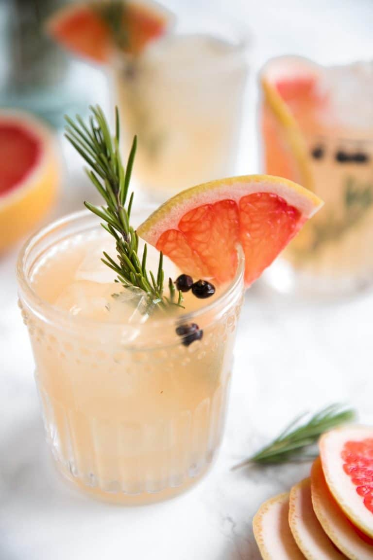 Glass filled with gin, elderflower liqueur, grapefruit juice, and fresh rosemary.