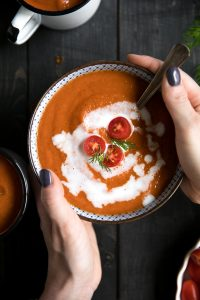 A person holding a bowl of food, with Roasted Red Pepper Soup and Tomato