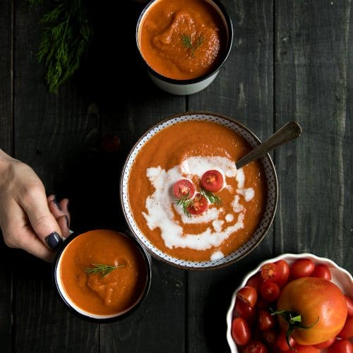 A person holding a plate of food on a wooden table, with roasted red pepper and tomato Soup