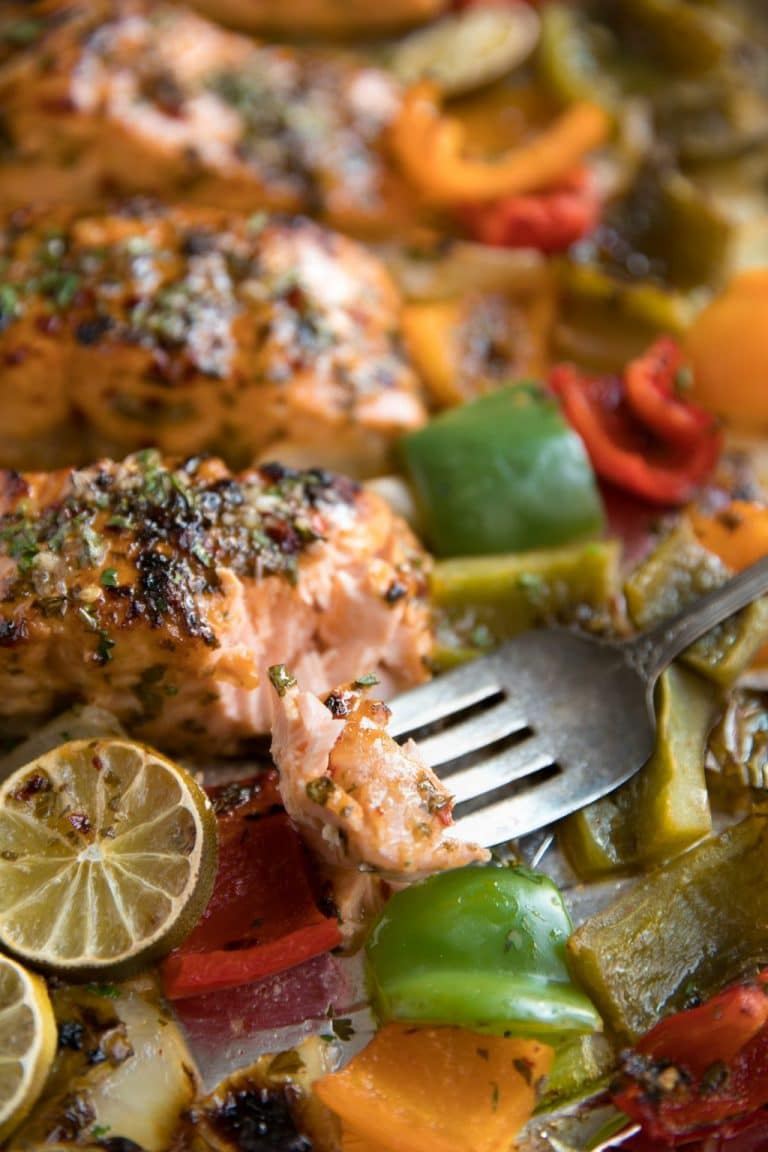 Sweet Chili Lime Orange Salmon with roasted bell peppers and onions baked on a single sheet pan.