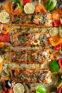 Large baking sheet with four salmon fillets baked in a marinade of orange juice and lime juice and sweet chili sauce with muli-colored bell peppers and onions..