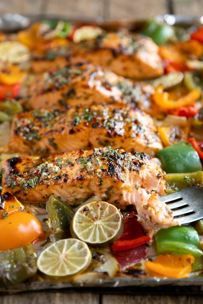 Image of a fork with a bite of tender cooked orange glazed salmon with four additional salmon fillets on a large baking sheet.