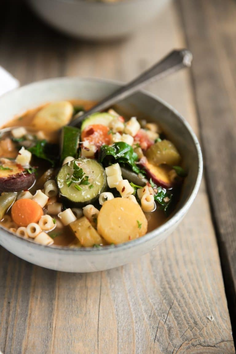 Gray bowl filled with minestrone soup made with carrots, green beans, zucchini, pasta, and garnished with parmesan cheese.