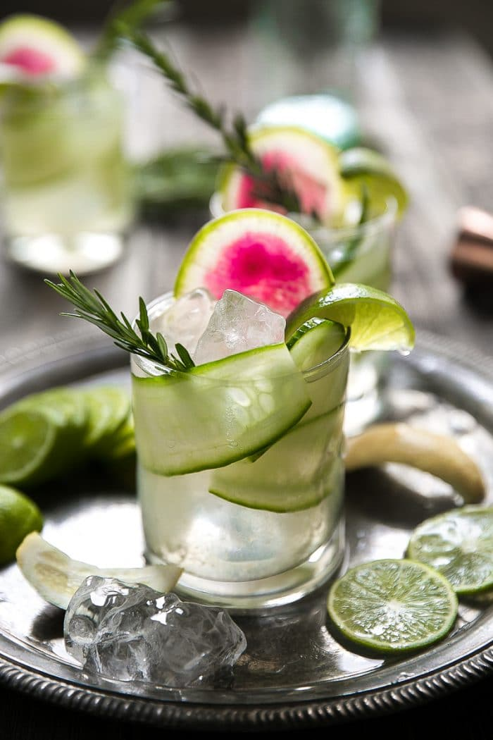 Gin and Tonic with cucumber, rosemary and watermelon radish on an antique tray.