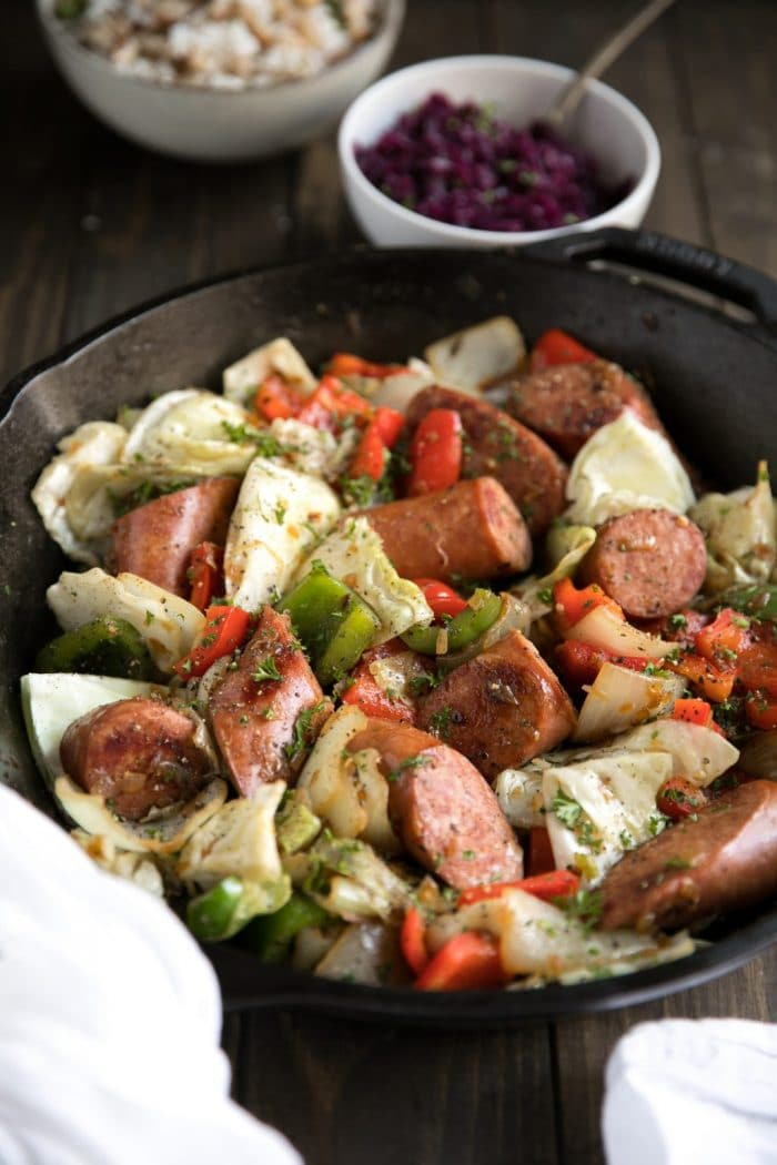 Large black cast iron skillet filled with cooked Kielbasa with Bell Peppers and Cabbage