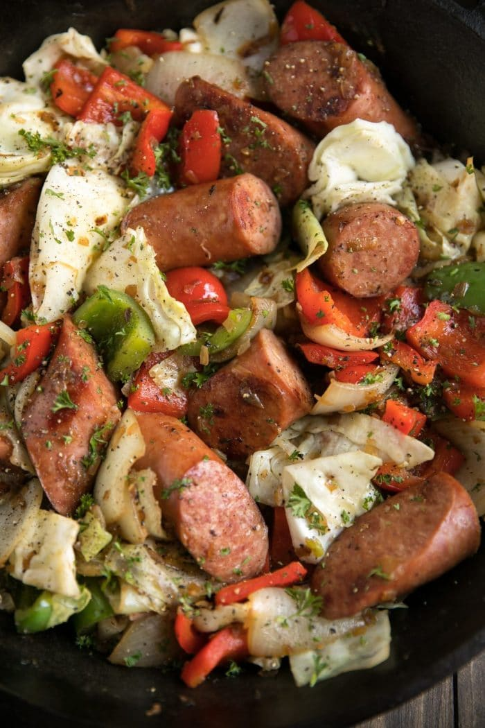 Large chunks of sauteed kielbasa, cabbage, red and green bell peppers, and onion all garnished with chopped parsley.