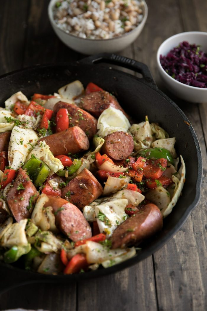 Black skillet with cooked onions, cabbage, kielbasa, and bell peppers.