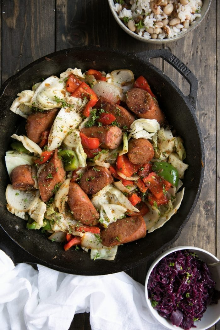Cast iron skillet filled with sauteed kielbasa, cabbage, bell peppers, and onion.