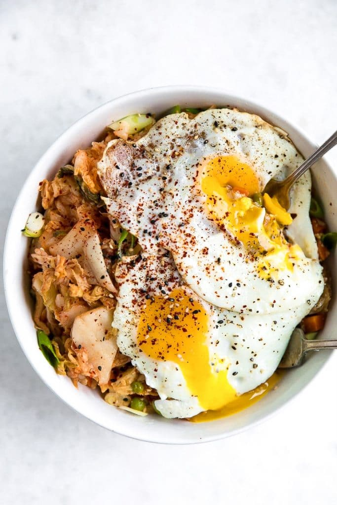 Overhead view of a white bowl filled with fried cauliflower rice with kimchi and two fried eggs