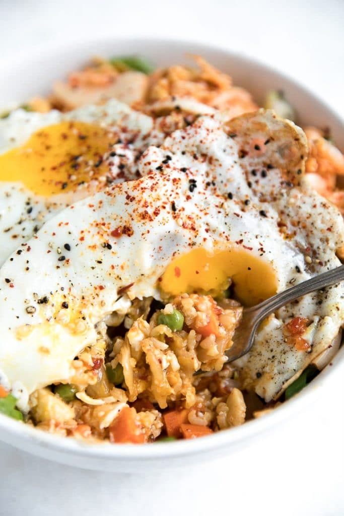 Half eaten bowl of Kimchi Cauliflower Fried Rice with two eggs