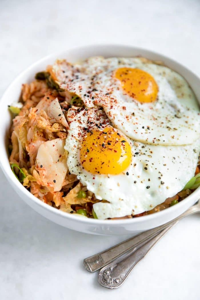Prepared bowl filled with kimchi, cauliflower rice, and two sunny-side-up eggs