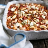 Fiber-filled white beans, sweet tomatoes, and tangy feta make this Tomato Baked Vegetarian Beans with Tangy Feta an easy and healthy anytime dinner loved by the whole family. Serve with homemade parsley pesto and fresh, crusty bread for an unforgettable Meatless Monday dish.