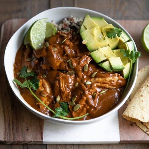 Mole sauce served with shredded chicken over rice with avocado and fresh lime.