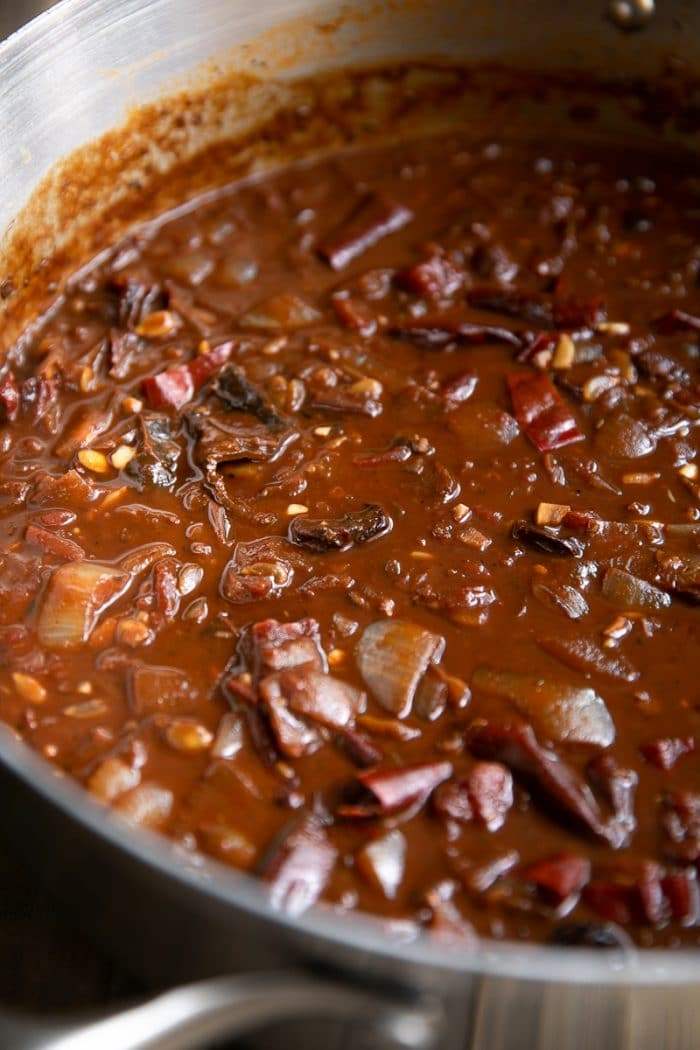 Mole sauce simmering in a large pot before blending.