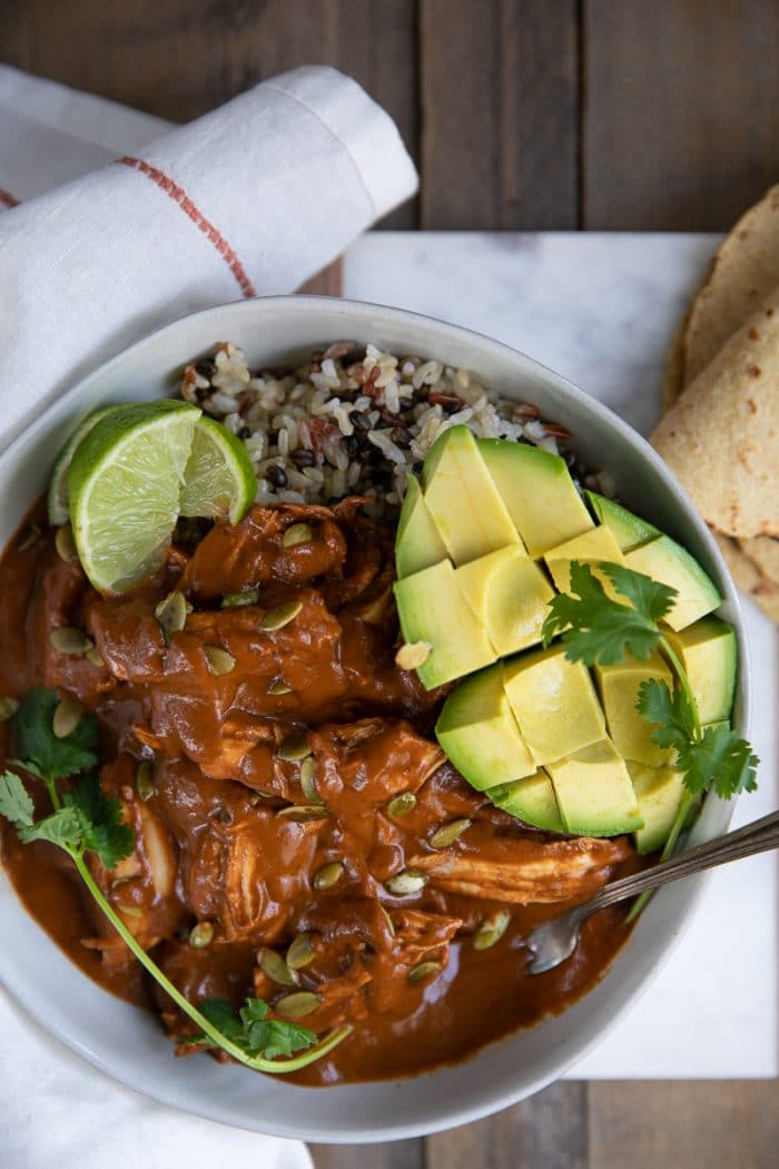 White bowl filled with Shredded chicken mole over rice and served with avocado and tortillas.