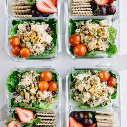 four meal prep containers with chicken salad