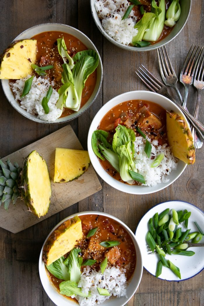 Four white bowls filled with a rich and creamy Thai fish curry topped with white rice, bok choy, and pineapple.