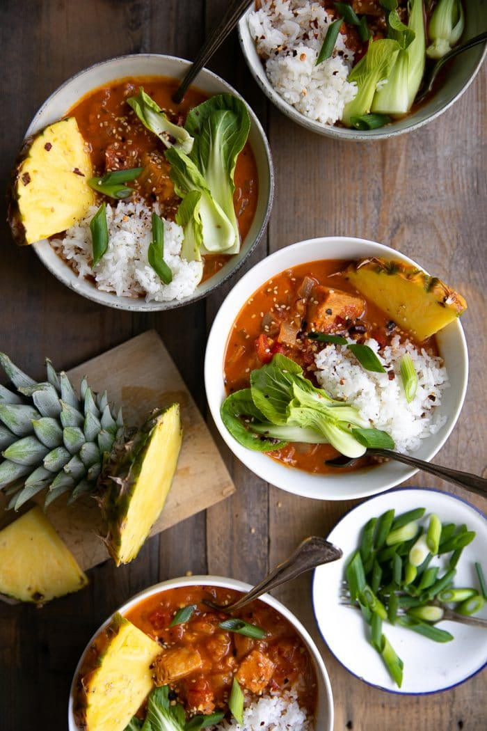 Four bowls filled with Red Thai fish curry and garnished with baby bok choy, white rice, and fresh pineapple.