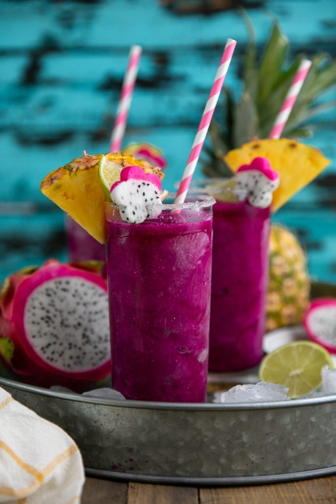 Frozen Dragon Fruit Margaritas on tray with straw