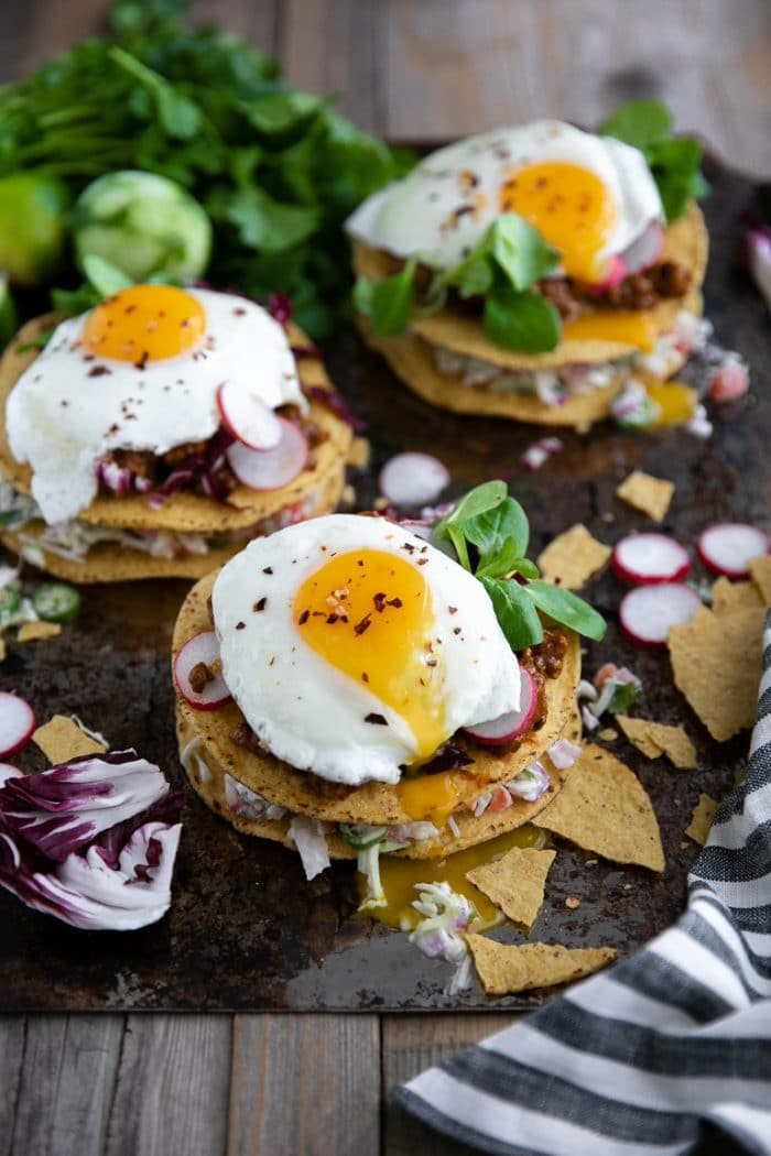 Three tostadas on a tray with drippy egg yolks and ground turkey in Molé sauce