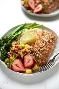 A plate of food with broccoli, with salmon crusted with Macadamia and Mango
